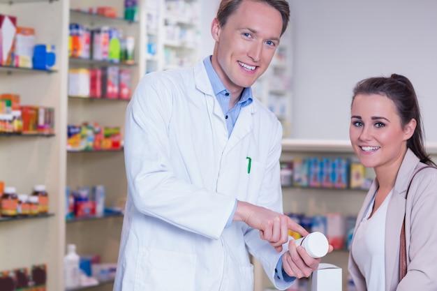 Souriant pharmacien expliquant les pilules au patient