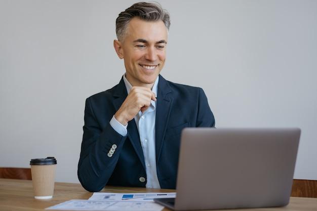 Souriant pigiste travaillant à domicile. bel homme d'affaires mature utilisant un ordinateur portable. entreprise prospère