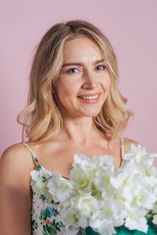 Souriant portrait de blonde jeune femme tenant des fleurs fraîches blanches sur fond coloré