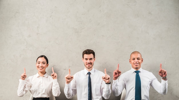 Souriant portrait d'une femme d'affaires et homme d'affaires pointant leurs doigts vers le haut contre le mur gris