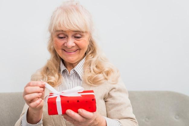 Souriant portrait d'une femme senior blonde ouvrant la boîte cadeau rouge