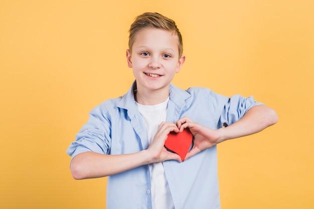 Souriant portrait d'un garçon montrant la forme de coeur rouge debout sur fond jaune