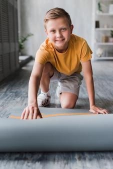 Souriant portrait d'un garçon posant un tapis d'exercice sur le sol