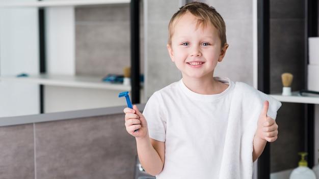 Souriant portrait d'un garçon tenant un rasoir bleu à la main montrant le pouce en haut signe