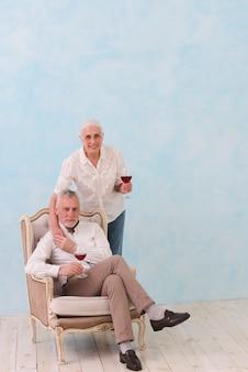 Souriant portrait d'un homme senior assis sur une chaise avec sa femme debout derrière un verre de vin