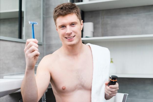 Souriant portrait d'un homme torse nu tenant une serviette blanche sur les épaules tenant un rasoir bleu et tondeuse à la main