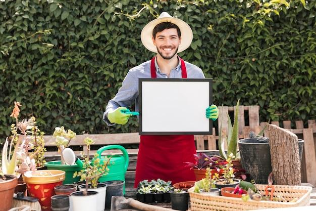 Souriant portrait d'un jardinier mâle pointant du doigt sur un cadre blanc vierge