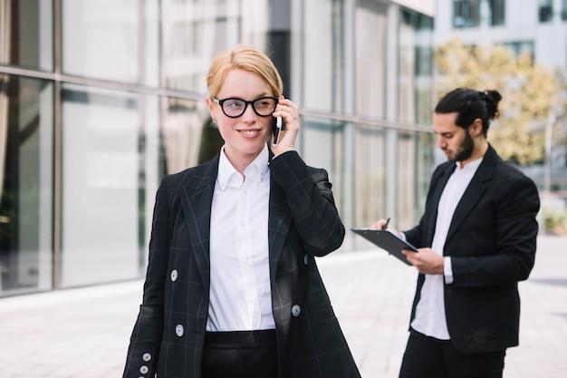 Souriant portrait d'une jeune femme d'affaires, parler au téléphone portable avec homme écrit sur le presse-papiers