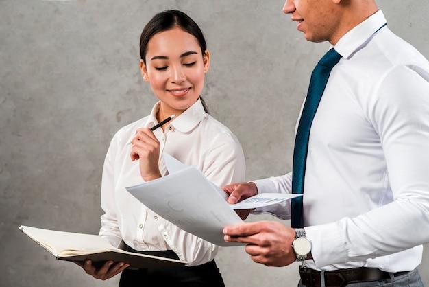 Souriant portrait d'une jeune femme d'affaires tenant un journal dans la main en regardant des documents tenus par son collègue