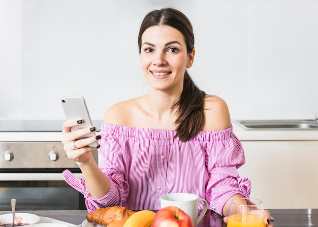 Souriant portrait d'une jeune femme à l'aide de téléphone portable avec petit-déjeuner sur la table