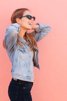 Souriant portrait d'une jeune femme portant des lunettes de soleil sur fond rose