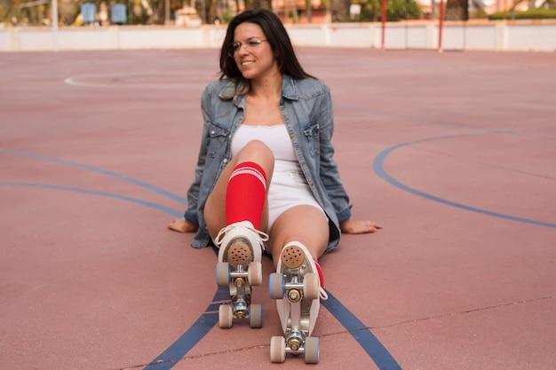 Souriant portrait d'une jeune femme portant des patins à roulettes relaxant sur le court