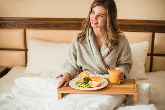 Souriant portrait d'une jeune femme prenant son petit déjeuner au lit