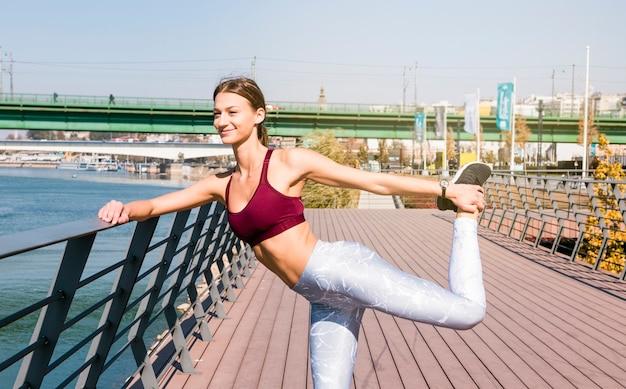 Souriant portrait d'une jeune femme qui s'étend de sa jambe debout sur le pont
