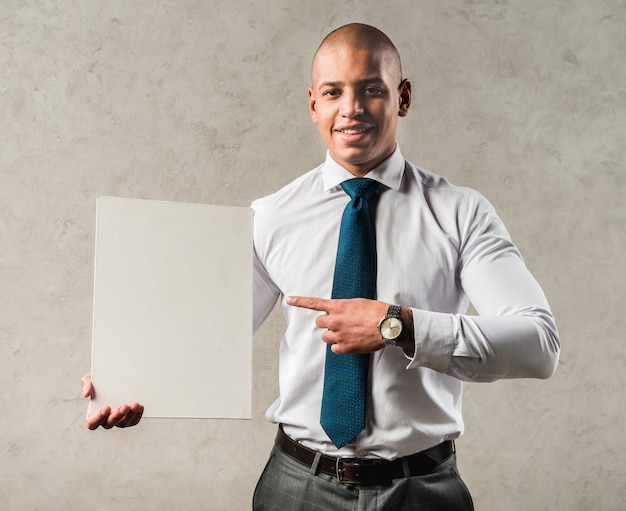 Souriant portrait d'un jeune homme d'affaires pointant son doigt vers une plaque vierge