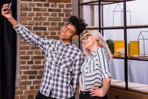 Souriant portrait d'un jeune homme africain prenant selfie sur téléphone mobile avec sa petite amie