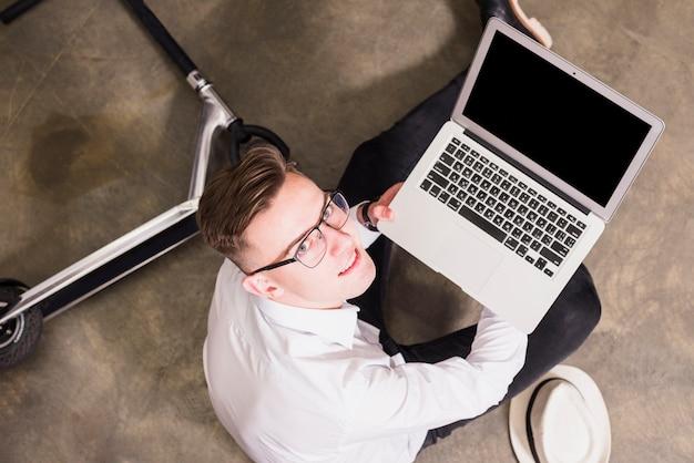 Souriant portrait d'un jeune homme assis sur le sol montrant un ordinateur portable