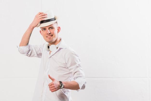 Souriant portrait d'un jeune homme avec un chapeau sur la tête montrant le pouce en haut signe