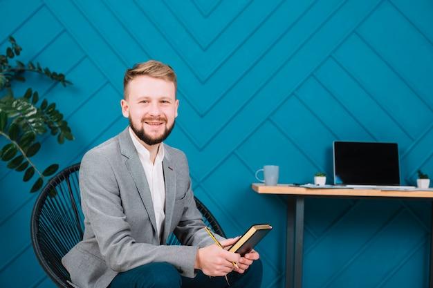 Souriant portrait d'un jeune psychologue assis sur une chaise, tenant un journal et un crayon à la main