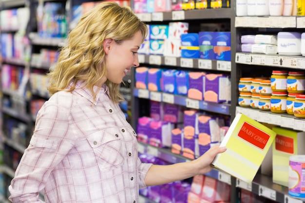 Souriant pretyt femme regardant un produit dans un supermarché