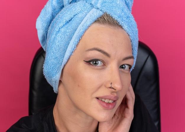 Souriant regardant la caméra jeune belle fille enveloppée de cheveux dans une serviette tenant une caméra isolée sur fond rose