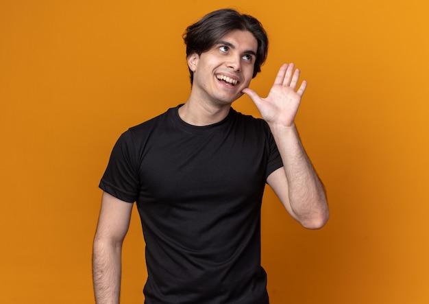 Souriant regardant le côté jeune beau mec portant un t-shirt noir tenant la main autour du visage isolé sur un mur orange