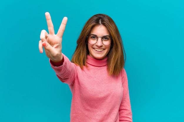 Souriant et regardant heureux, insouciant et positif, signe de victoire ou de paix d'une seule main
