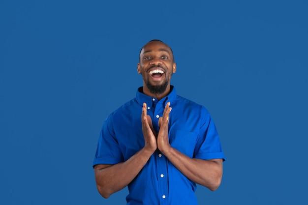 Souriant, riant. portrait monochrome de jeune homme afro-américain isolé sur le mur bleu du studio.