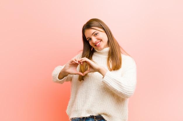 Souriant et se sentant heureux, mignon, romantique et amoureux, en forme de cœur avec les deux mains