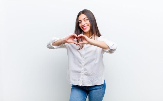 Souriant et se sentir heureux, mignon, romantique et amoureux, en forme de coeur à deux mains