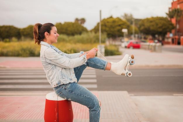 Souriant séduisante jeune femme assise dans la rue attachant la dentelle de patin à roulettes