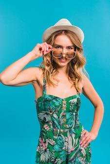 Souriant séduisante jeune femme en robe à fleurs et chapeau tenant des lunettes de soleil