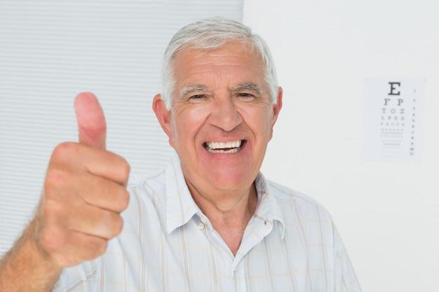 Souriant senior homme gesticulant pouce en l'air avec le tableau de l'oeil en arrière-plan