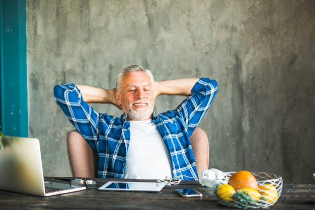 Souriant senior homme reposant sur une chaise avec dispositif électronique sur la table
