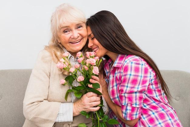 Souriant senior mère penchant sa tête sur les épaules de sa mère senior tenant des roses