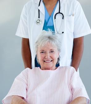 Souriant senior patient assis sur un fauteuil roulant
