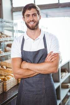 Souriant serveur en tablier bras croisé
