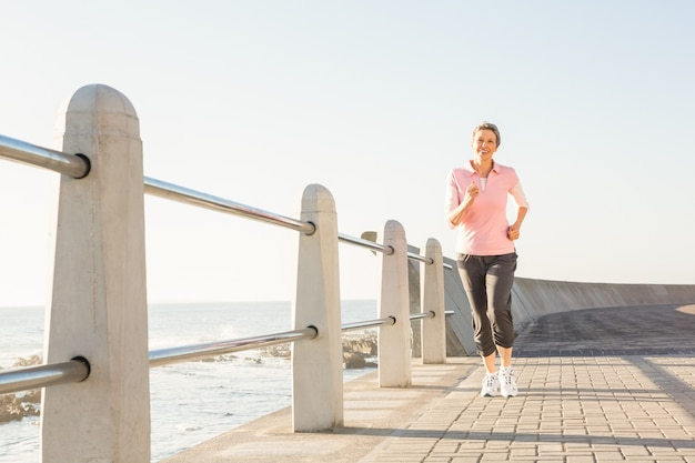 Souriant sportif femme jogging sur la promenade