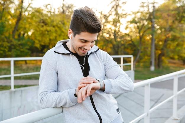 Souriant sportif sain debout à l'extérieur à la balustrade, regardant la montre intelligente