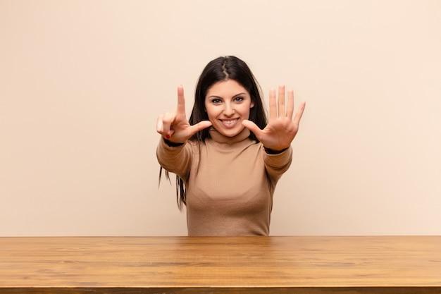 Souriant et sympathique, montrant le numéro sept ou septième avec la main en avant, le compte à rebours