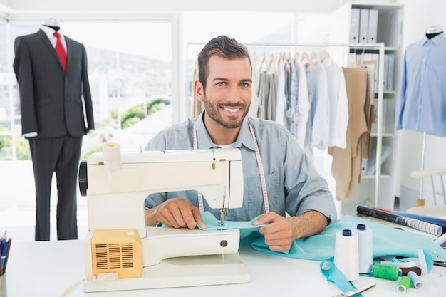 Souriant tailleur masculin coudre dans l'atelier