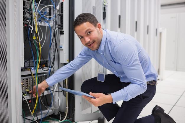 Souriant technicien avec tablette pc brancher les câbles dans le serveur dans le centre de données