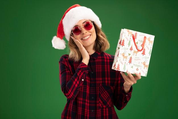 Souriant tête inclinable jeune belle fille portant un chapeau de noël avec des lunettes tenant un sac cadeau mettant la main sur la joue isolé sur un mur vert avec espace copie