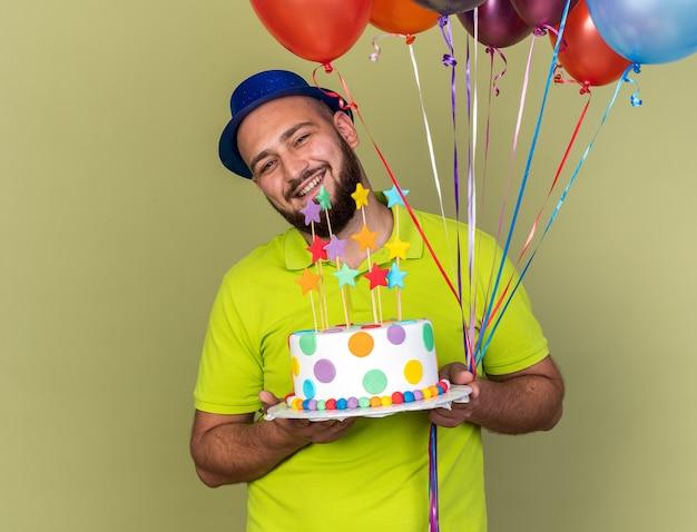 Souriant tête inclinable jeune homme portant un chapeau de fête tenant des ballons avec un gâteau