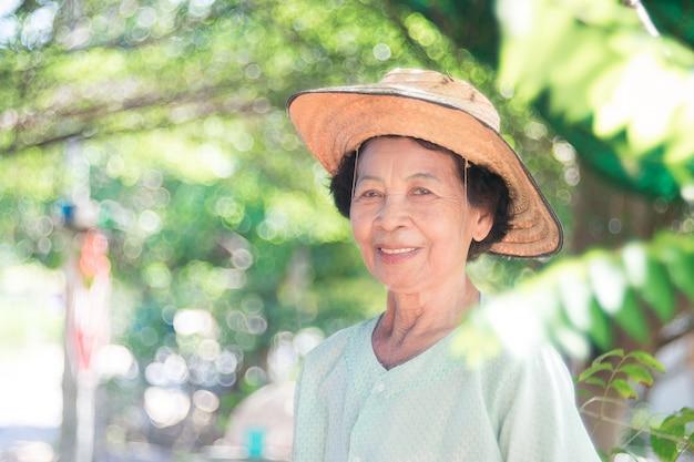 Souriant vieille femme d'agriculteur asiatique permanent avec heureux.