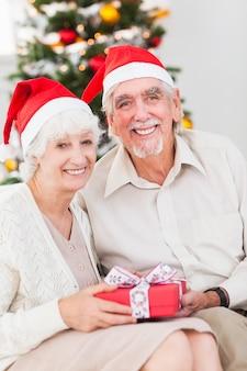 Souriant vieux couple échangeant des cadeaux de noël