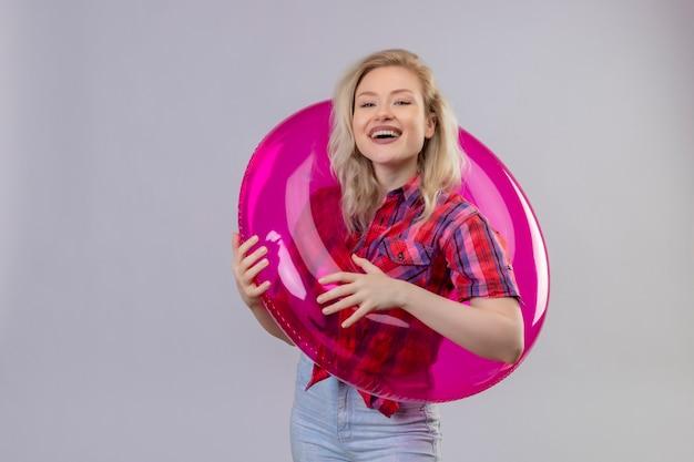 Souriant voyageur jeune fille portant une chemise rouge en anneau gonflable sur fond blanc isolé
