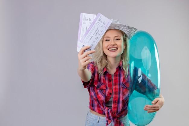 Souriant voyageur jeune fille portant une chemise rouge au chapeau tenant une bague gonflable et des billets sur fond blanc isolé