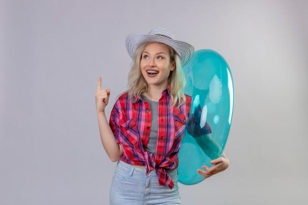 Souriant voyageur jeune fille portant une chemise rouge au chapeau tenant des points de l'anneau gonflable vers le haut sur fond blanc isolé