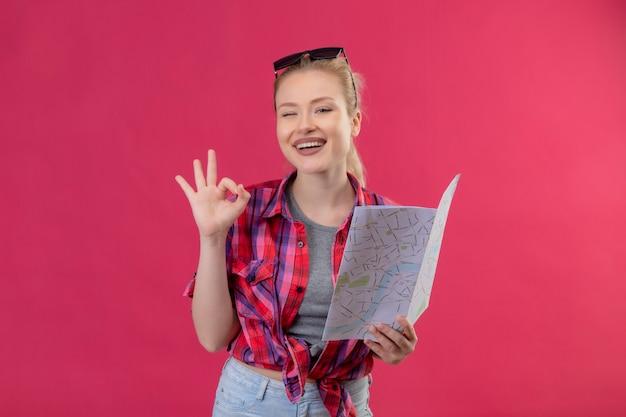 Souriant voyageur jeune fille portant une chemise rouge et des lunettes sur sa tête tenant la carte montrant le geste okey sur fond rose isolé